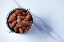 Almonds In Zinc Bucket, Viewpoint On A Marble Background