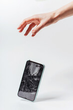 Smartphone Falling Out Of Hand On A White Background. Crash Protective Tempered Glass For Smartphone. Smartphone With Broken Screen Falls Out Of Hand