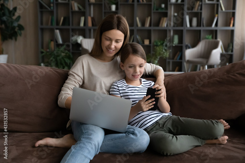 Fototapeta Happy Caucasian mom relax on sofa work online on laptop gadget, small teen daughter play app game on cellphone. Young mother and little girl child rest together browsing using devices at home. obraz