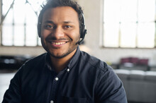 Close-up Portrait Of Cheerful Indian Guy Wearing Wireless Headset Looks At The Camera With Toothy Smile, Video Connect With Multiracial Colleague, Video Chat With Hindu Guy In Headphones, Webcam View