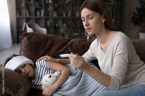 Fotografija Worried young mother take care of sick small daughter feel unhealthy, check measure high temperature with thermometer