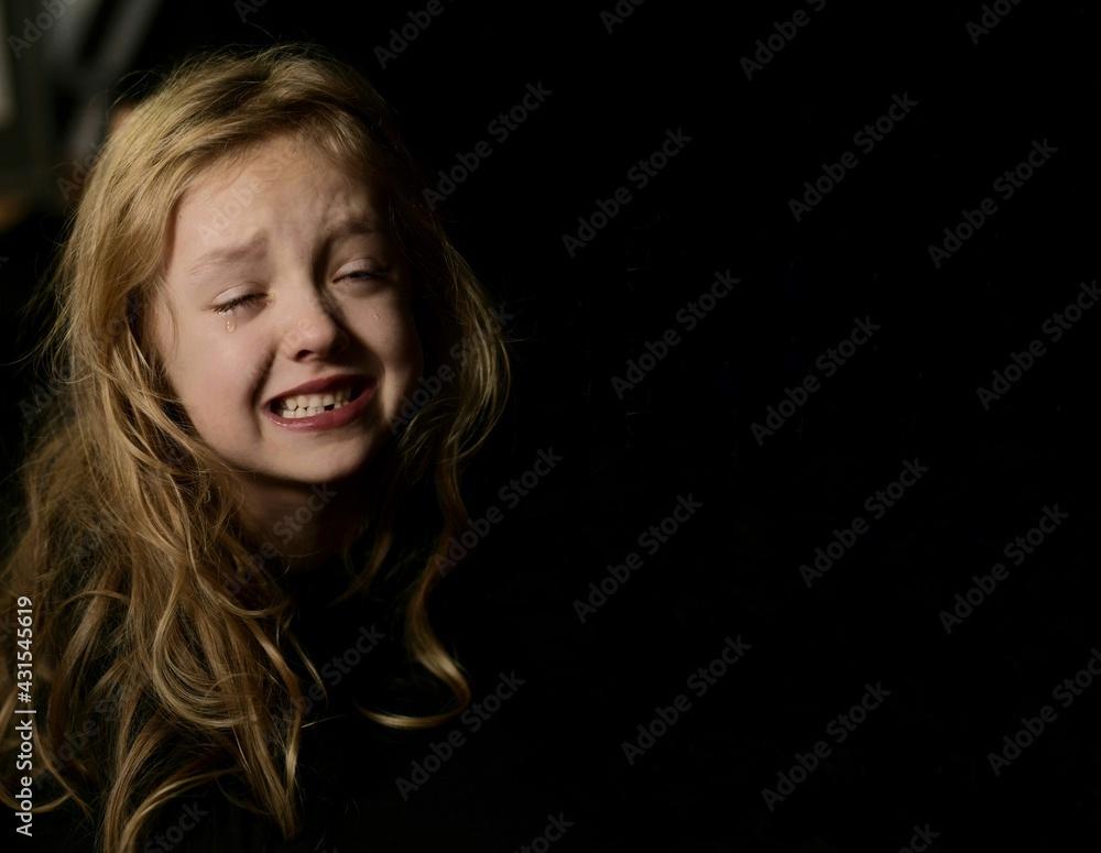 Fototapeta Mała dziewczynka ubrana na czarno, łzy spływają po policzkach, portret horyzontalny na czarnym tle. Tylko twarz.