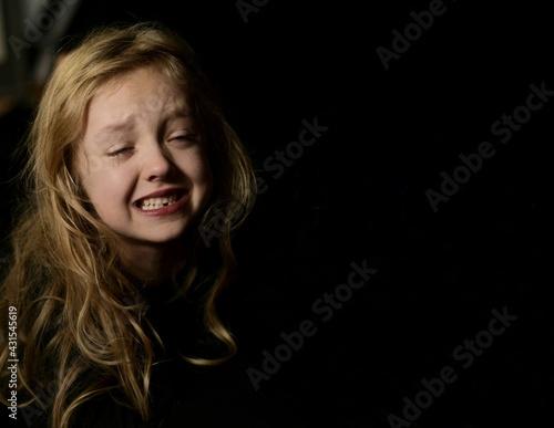 Mała dziewczynka ubrana na czarno, łzy spływają po policzkach, portret horyzontalny na czarnym tle. Tylko twarz. - fototapety na wymiar