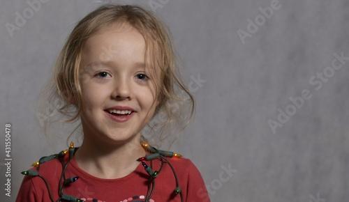 Śliczna dziewczynka w wieku przedszkolnym, w czerwonej bluzce, siedzi, jasne tło, portret horyzontalny.    - fototapety na wymiar