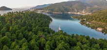 Aerial View Of A Wooden Sailing Boat Anchored In A Small Picturesque Harbor. Amazing Greek Beauty Of Skopelos, Greece