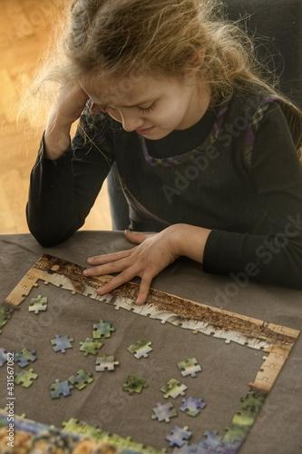 Dziewczynka w wieku przedszkolnym, ubrana w ciemny strój, podparta łokciem o stól, uklada puzzle. Frustracja na twarzy. Portret wewnątrz.  - fototapety na wymiar
