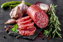 Traditional Smoked Salami Sausage With Spices.Salami Sausage Slices On A Black Chopping Board. Dark Background.