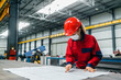 canvas print picture Women in protective work wear looking at blueprints at industry hall.
