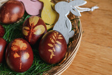 Easter Eggs Naturally Dyed With Onion Skins. Brown Easter Eggs First Wrapped In Nylon Stockings That Hold A Leaf And Then Boiled In Water And Onion Skins. Eggs On Grass In Basket With Wooden Bunnies