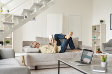 Older Senior Man Wearing Glasses Reading Book Relaxing Lying On Couch At Home. Middle Aged 50 Years Old Man Enjoying Leisure Time Daily Activity And Lounge On Sofa In Modern Apartment Living Room.