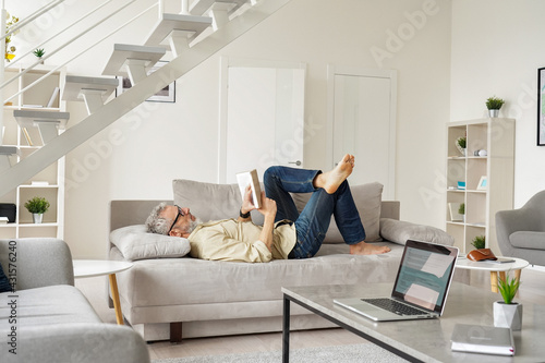Cuadros en Lienzo Older senior man wearing glasses reading book relaxing lying on couch at home