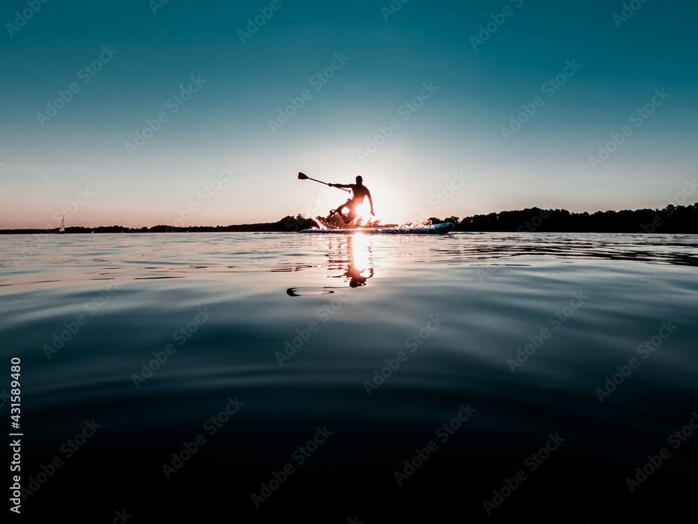 Fototapeta Mężczyzna wywracający się na desce SUP nad jeziorem o zachodzie słońca