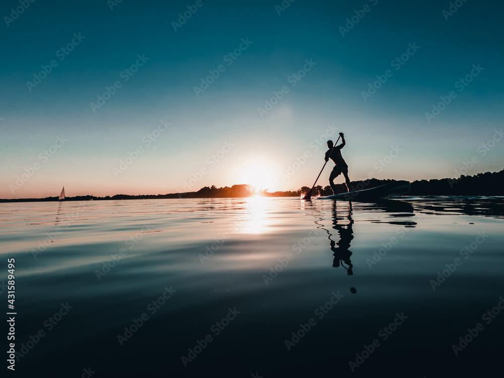 Fototapeta Mężczyzna na desce SUP o zachodzie słońca nad jeziorem
