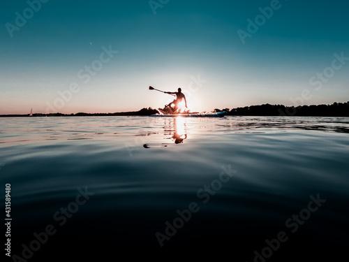 Obraz Mężczyzna wywracający się na desce SUP nad jeziorem o zachodzie słońca - fototapety do salonu