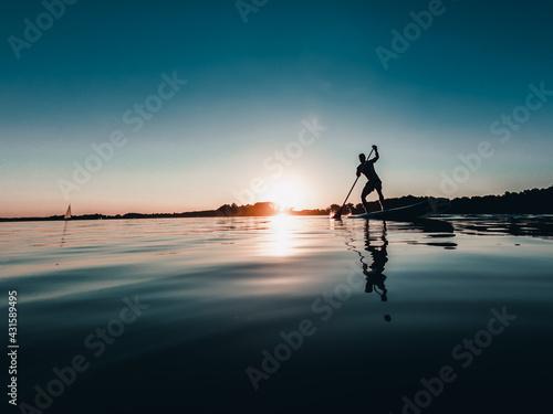 Obraz Mężczyzna na desce SUP o zachodzie słońca nad jeziorem - fototapety do salonu