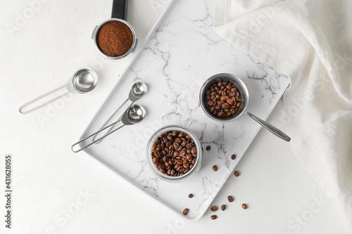 Obraz Jar and pot with coffee beans on light background - fototapety do salonu