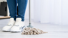 Cleaning Service. Housework Company. Home Chores. Advertising Background. Unrecognizable Woman Legs In Jeans Sneakers Shoes Staying With Mop Copy Space.
