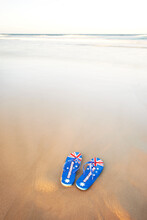 Jandals, Thongs, With Australian Flag On The Sand With Waves In The Background