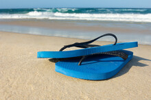 Blue Flip Flops Resting On Sand With Ocean In Background