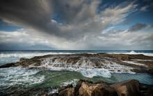 Stormy Skies And Waves Crashing Onto Rocky Coast