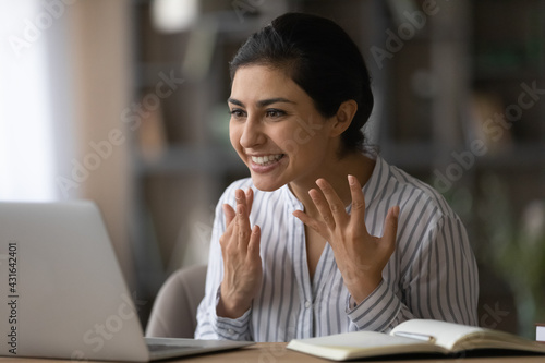 Fototapeta Close up overjoyed Indian woman looking at laptop screen, reading good news in email message, received money refund, job promotion or great exam results, excited businesswoman making video call obraz