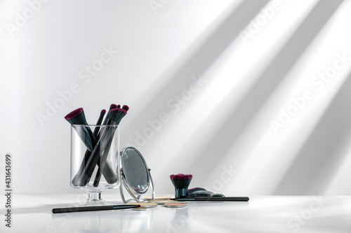 Fotografia Set of cosmetic brushes on a white background and table in the morning sun