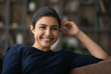 Close Up Positive Indian Woman Relaxing On Couch, Having Fun, Happy Young Female With Healthy Toothy Smile Looking In Distance, Watching Comedy Movie On Tv, Enjoying Leisure Time At Home Alone