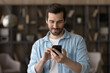 Leinwandbild Motiv Close up satisfied man using phone, looking at screen, standing at home, positive young male holding smartphone, chatting in social network with friends or shopping online, enjoying leisure time