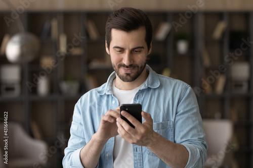 Photo Close up satisfied man using phone, looking at screen, standing at home, positiv