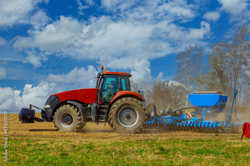 Fotografie, Obraz A farmer with a seeder on a tractor - sowing grain in an agricultural field