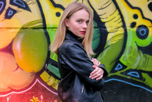 Young Blonde Woman Next To Graffiti Wall. Street Art And Contemporary Painting Process. Street Lifestyle. Stylish Leather Jacket And Red Lips.