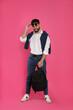 Leinwandbild Motiv Young man with stylish backpack on pink background