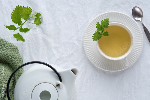 Obraz Nettle tea cup, fresh stinging nettle herbs. Flat lay, top view, off white textile tablecloth. White ceramic teapot. Natural light. - fototapety do salonu