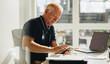 Leinwandbild Motiv Senior businessman using mobile phone at work