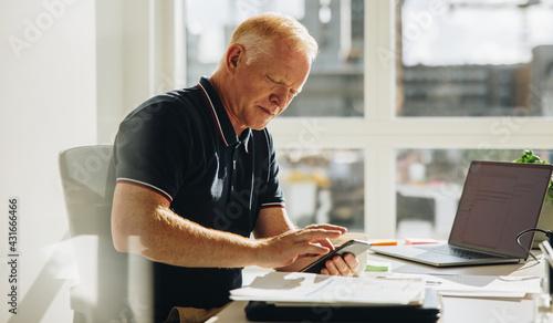 Fototapeta Senior businessman using mobile phone at work obraz