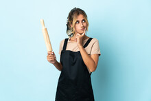 Young Blonde Uruguayan Cooking Woman Isolated On Blue Background And Looking Up