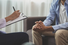 Asian Young Man, Male Has Mental Symptoms Which Must Have Been Therapy And Stress, Sitting On Couch To Consult To Psychologist During The Session  Taking Notes To Find Out How To Treat The Therapist.