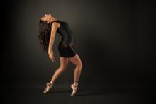 Hispanic Pregnant Ballerina Performing Classical Ballet Pose With Bodysuit And Black Skirt In Studio
