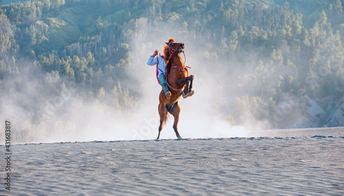 Fototapeta Red horse rearing up on desert with  unidentified horse rider - Bromo, Indonesia obraz