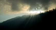 Sun Is Ready To Set Behind The Mountains And Giving Rays Of Light Though The Fog & Trees.