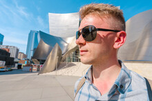 A Young Blond Man In Sunglasses Stands On The Steps Of The Walt Disney Concert Hall. Business Style In A Trendy Building, Los Angeles