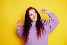 Woman In A Purple Sweater On A Yellow Background Posing. A Beautiful Brunette With Long Curly Hair And Red Roots. The Model Looks At The Camera And Dancer, Rejoices, Has Fun