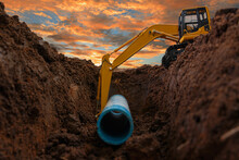 Crawler Excavator Is Digging In The Construction Site Pipeline Work On Sunset Sky Background