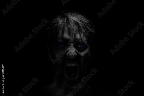 Fototapeta Portrait of scary man screaming, possessed, zombie.