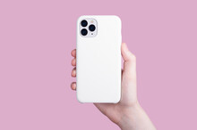 Female Hand Holding White IPhone 11 Pro In Soft Silicone White Cover Back View . Phone Case Mock Up Isolated On Pink Background , IPhone 12