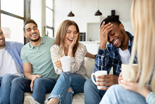 Having Fun With Friends. Group Of Young Multiracial People Drinking Coffee At Home, Joking And Laughing Together
