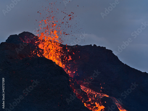 Fotografia, Obraz Stunning closeup view of erupting volcano in Geldingadalir valley near Fagradalsfall mountain, Grindavík, Reykjanes peninsula, southwest Iceland with ejection of hot, glowing lava in the evening