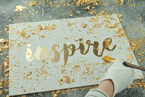 Inspire. Motivating lettering on white board. Handmade creativity. Gold letters. Gilding. Brush in hand