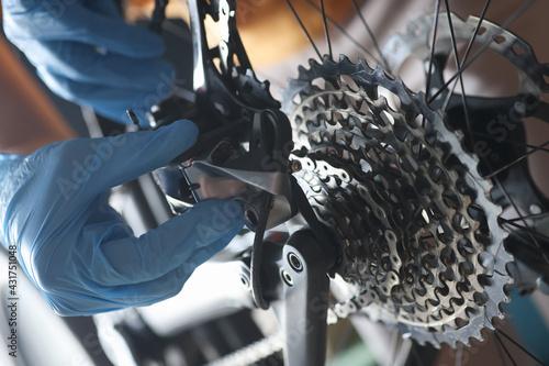 Gloved handyman repairs rear bicycle cassette closeup - fototapety na wymiar
