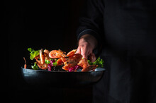 Chef Prepares Shrimp With Herbs. Cooking Seafood, Healthy Vegetarian Food And Food On A Dark Background. Free Advertising Space